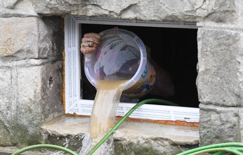 Eimer Wasser aus Kellerfenster