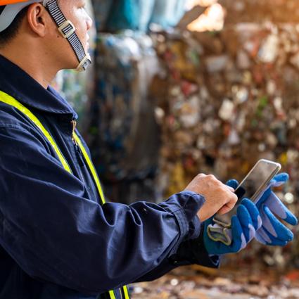 Smartphone vor Press-Müll-Ballen